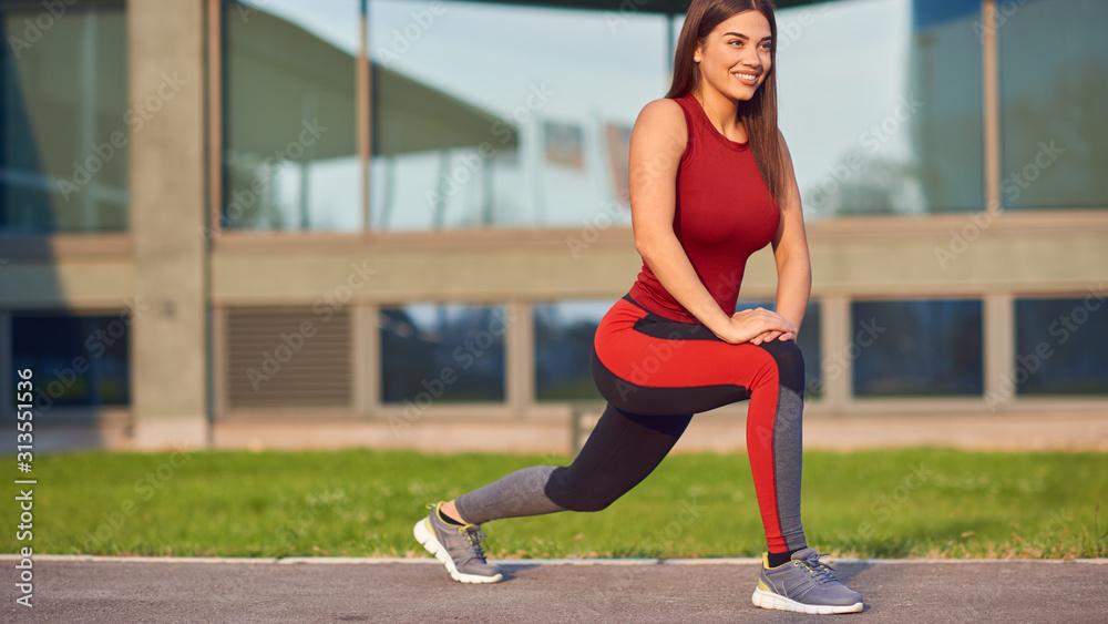 Fototapeta Young woman exercising / stretching in urban park.
