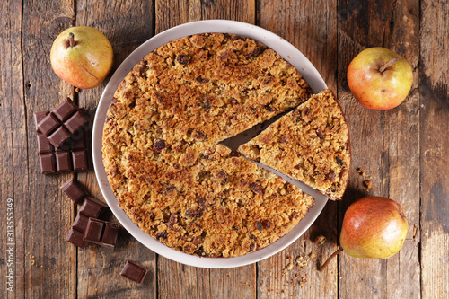Valokuva crumble with pear and chocolate on wood background