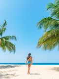 Beach vacation tourist enjoying Caribbean cruise travel destination walking in bikini on vertical blue sky background and palm trees, happy woman relaxing in Barbados.