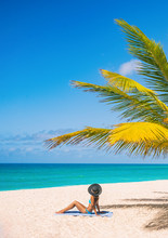 Caribbean Beach Tourist Relaxing In Barbados, Cruise Shore Day. Woman Sunbathing Sun Tanning Under Palm Tree On Sand On Dover Beach, Famous Resort Tourist Tropical Destination.