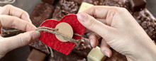 Appetizing Food Background. Assortment Of Chocolate Handmade Candy And Red Heart Card For Valentine's Day In Female Hands. Chocolate Background.
