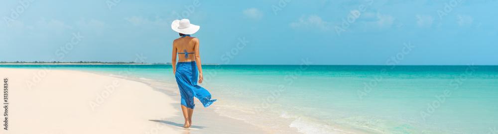 Fototapeta Luxury beach vacation elegant tourist woman walking relaxing in beachwear hat on white sand Caribbean beach. Lady tourist on holiday vacation resort. Banner panorama landscape.
