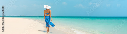 Luxury beach vacation elegant tourist woman walking relaxing in beachwear hat on white sand Caribbean beach. Lady tourist on holiday vacation resort. Banner panorama landscape.