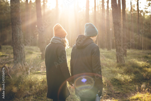 Couple in warm clothing taking a walk inside a sunny forest Wallpaper Mural