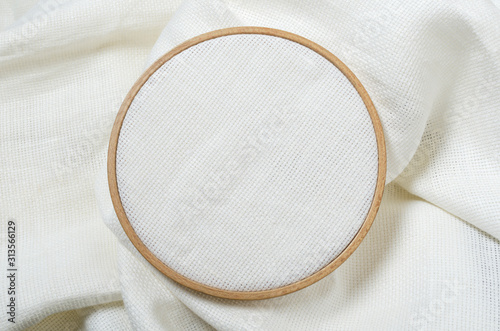 Fototapeta Closeup of wooden embroidery hoop and clean white fabric for hobby needlework