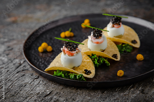 Fotografia Luxurious appetizer of quail eggs with a paste of squid, shrimp and black caviar on potato and cheese chips