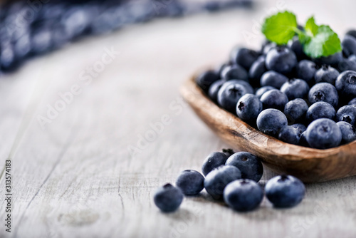 Fototapeta Freshly picked blueberries in wooden bowl on white table. Juicy and fresh blueberry with green leaves at rustic board. Bilberry antioxidant healthy forest food. obraz