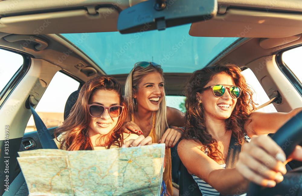 Fototapeta Three female friends enjoying traveling at vacation in the car.