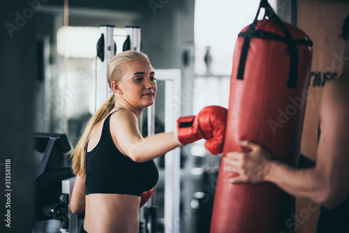 Fotografía  An athletic woman boxer hitting the punching bag in the gym