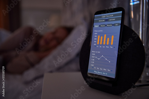 Woman Sleeping In Bed With Sleep Data App Running On Mobile Phone On Bedside Wallpaper Mural