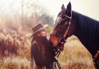 Portrait of woman and horse outdoors. Woman stroking a horse.