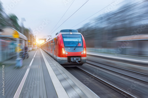 Cuadros en Lienzo Passenger high speed red train with motion blur in station.