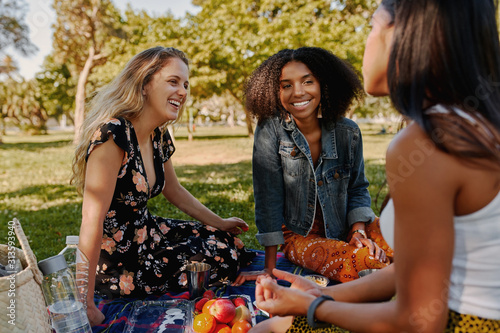 Group of smiling multiracial female best friends sitting together on blanket wit Fotobehang