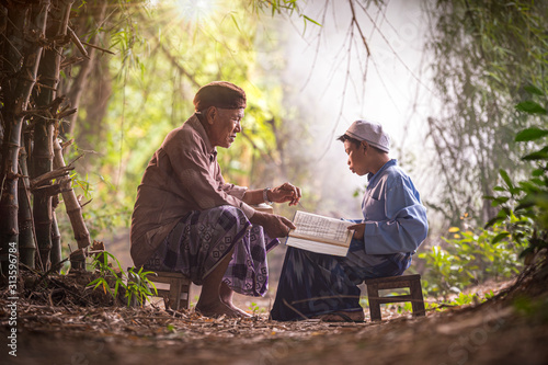 Vászonkép Muslim grandfather is teaching nephew to read a book