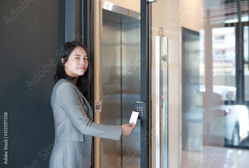 Photo Door access control - young officer woman holding a key card to lock and unlock door for access entry