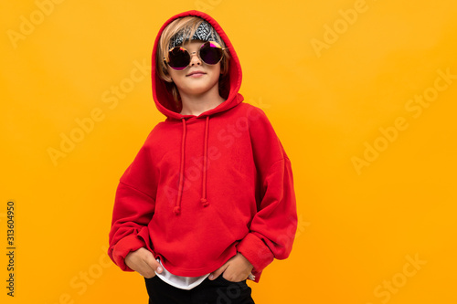 Papel de parede blond boy with a bandana on his head in a red hoodie and glasses posing on an or