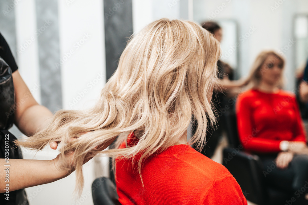 Fototapeta Beautiful hairstyle of woman after dyeing hair and making highlights in hair salon.