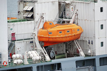 Red Lifeboat Docked To Ship
