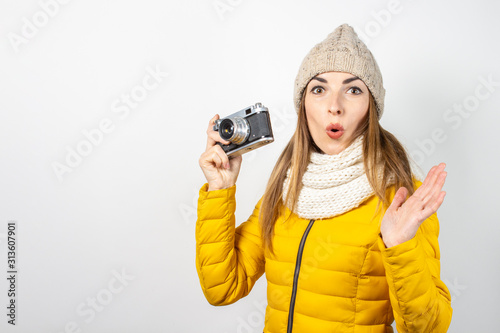 Fotografia, Obraz Young woman with a surprised face in a yellow down jacket and hat holds a camera in her hands on a light background
