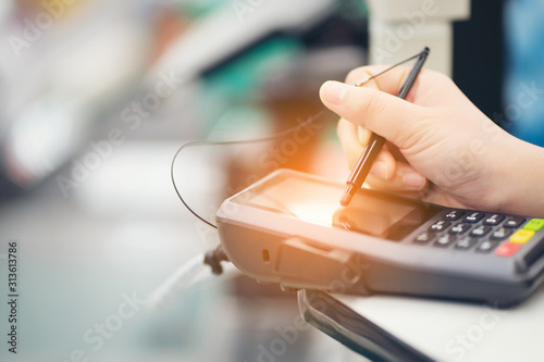 Fotomural Close-up of consumer's women hand signing on a touch screen of credit card sale