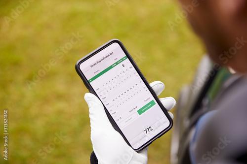 Fototapeta Close Up Of Male Golfer In Buggy Checking Score On Mobile Phone App obraz