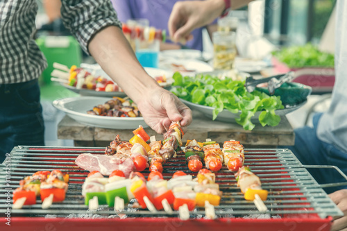 Fotomural A man grilling pork and barbecue in dinner party