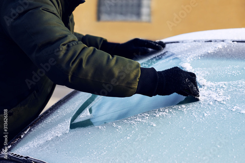 Obraz Man scraping ice from the windshield of a car covered wit hoarfrost - fototapety do salonu