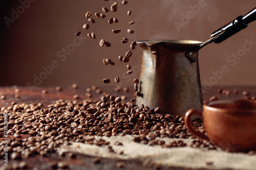 Obraz na plátně Falling coffee beans and old copper coffee maker.