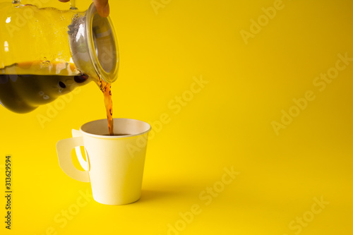 Fototapeta Hand pouring liquid coffee put in the cup on a yellow paper background. Copy space for your text. obraz