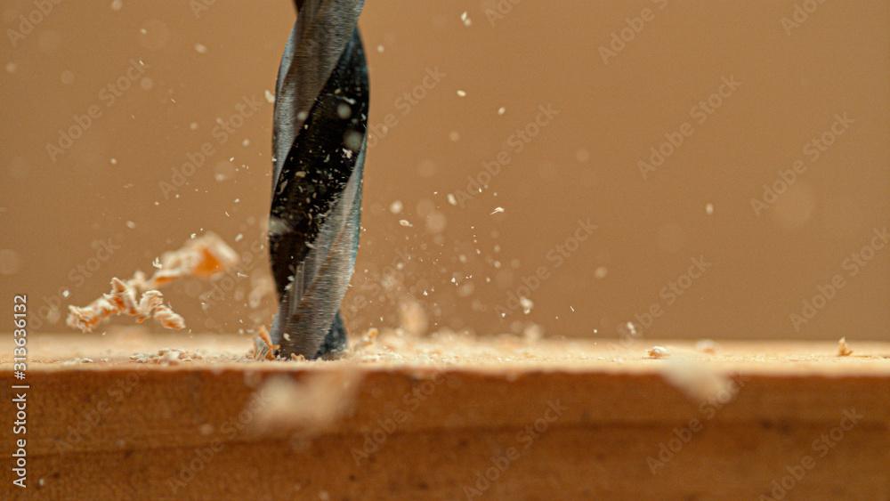 Fototapeta MACRO: Wood chips fly off a plank as handyman drills holes into the workpiece.