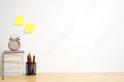 Office desk with pencils, alarm clock and book on wood table. work copy space.
