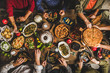 Traditional Turkish family celebration dinner. Flat-lay of people feasting at table with Turkish salads, cooked vegetables, meze starters, pastries and raki drink, top view. Middle Eastern cuisine