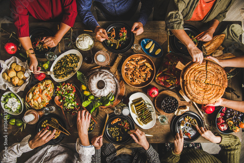 Fototapeta Traditional Turkish family celebration dinner. Flat-lay of people feasting at table with Turkish salads, cooked vegetables, meze starters, pastries and raki drink, top view. Middle Eastern cuisine obraz