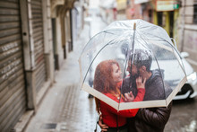 Couple In Love Under Transparent Umbrella In The City