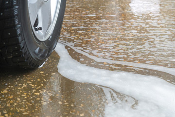 a close-up view of civil car wheel in soap puddle on the floor of washing garage