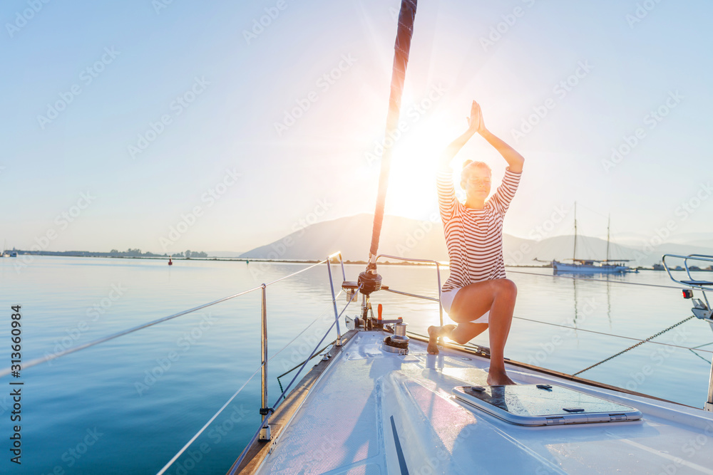 Fototapeta Girl is practicing yoga on the deck of the yacht boat