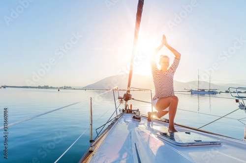 Obraz Girl is practicing yoga on the deck of the yacht boat - fototapety do salonu