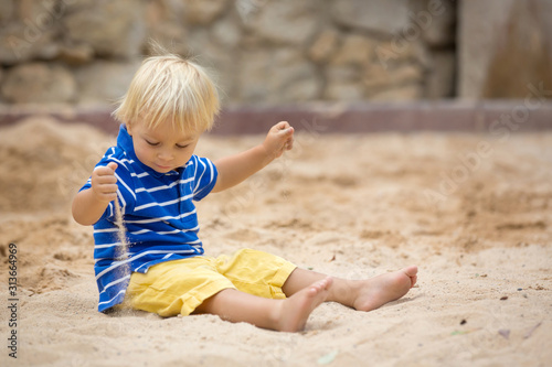 Obraz na plátně Little toddler boy, playing with sand in sandpit at the playground