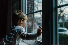 A Little Boy Looks Out A Window.