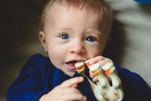 A Baby Boy Chews On A Toy.