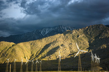Windmills Are Illuminated In Front Of The Snow Peaked Mountains In The Yucca Valley