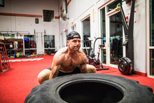 Muscular Man Lifts Large Tire At The Gym