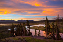 Man Taking A Photo At Yellowstone River In Hayden Valley At Sunset