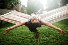 Tween Girl Taking A Break While Swinging In Hammock In Backyard