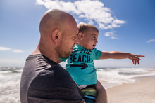 Father Holding Young Son At The Beach As Son Points Away From Ocean