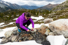 A Women Crouches Down And Uses A Water Filter To Get Drinking Water From A Small Alpine Stream In The Mountains Of British Columbia.
