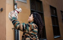 Woman Holding Her Dog Up In The Air Smiling