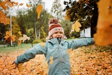 Young Girl Laughing And Throwing Fall Leaves Into The Air