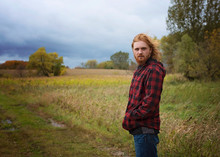 Young Man With Long Red Hair And Beard Outside In The Country