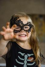 Little Smiling Girl In Mask Dressed For Halloween In Skeleton Costume